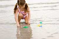 Girl playing with toys on the beach
