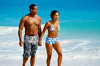 A couple walking near a seashore, Natural Arches Beach, Bahamas