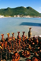 A variety of wooden souvenirs are displayed on a seashore, St. Maarten, Caribbean