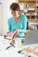 Woman looking through diary in home office