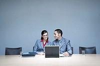 Businesswoman and businessman sitting at desk using laptop, smiling