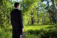 Businessman holding briefcase standing in wooded marshland, rear view