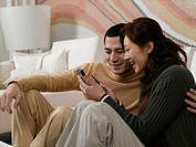 Young couple relaxing on sofa, woman showing man mobile phone