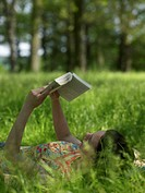 Young woman lying on grass reading book