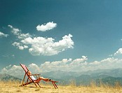 Boy (5-7) relaxing on deckchair in mountainous landscape