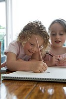 Two girls (4-6) drawing picture in sketch pad on table, smiling
