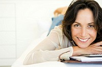 Woman lying on bed with diary and calculator, portrait, smiling