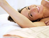 Woman lying on bed with newspaper, smiling, portrait