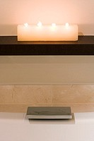 Candles on a shelf above a bathtub´s modern stopper hardware