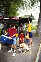 Parents and children (3-6) preparing for trip in van