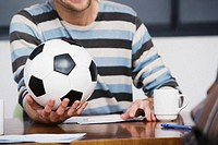 Businessman holding football during meeting, close-up