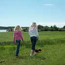 Two girls walking dog through field, rear view