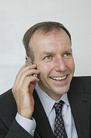 Mature man talking on mobile phone, looking up