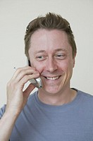 Mature man talking on cell phone, smiling