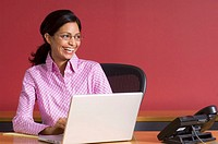 Businesswoman with laptop, looking away, smiling