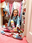 Girl (6-8) putting on shoes in closet, smiling, close-up