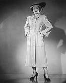 Woman wearing overcoat posing in studio (B&W), portrait