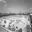People relaxing at outdoor swimming pool, (B&W), elevated view
