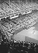 People in stadium watching baseball match, (B&W), elevated view