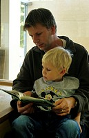 Boy sitting on his father´s lap while studying