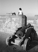 A girl sitting on a wall near the sea in Morocco