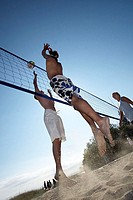 Low angle view of two young men with a young woman playing beach volleyball
