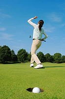 Young female golfer punching the air after holing out