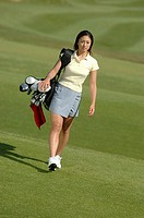Young Asian female walking across course with golf bag