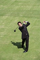 Young Asian businessman swinging golf club