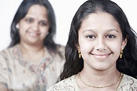 Portrait of a girl smiling with her mother standing behind her