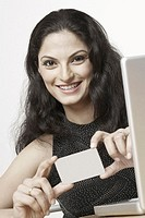 Portrait of a young woman sitting in front of a laptop and holding a credit card