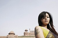 Low angle view of a young woman in front of a fort, Red Fort, Delhi, India