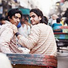 Rear view of two young men sitting in a rickshaw
