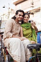 Young couple sitting in a rickshaw and taking a photograph of themselves