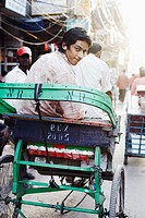 Rear view of a young man sitting in a rickshaw and listening to an MP3 player