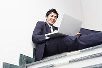 Low angle view of a businessman sitting on the staircase and using a laptop