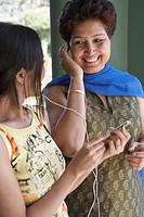 Close-up of a mother and her daughter listening to an MP3 player