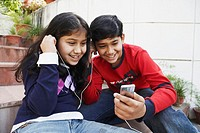 Close-up of a brother and his sister listening to an MP3 player (thumbnail)