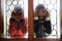 Close-up of two children peeking through a window