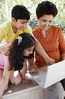 Close-up of a grandmother and her two grandchildren looking at a laptop
