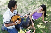 High angle view of a young man playing the mandolin with a young woman looking at him