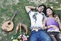 High angle view of a young couple lying together in the park (thumbnail)