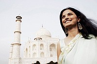 Close-up of a young woman standing in front of a mausoleum, Taj Mahal, Agra, Uttar Pradesh, India