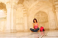 Young woman sitting on the floor in an archway