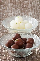 Close-up of Gulab Jamuns and Rasgullas in two bowls (thumbnail)