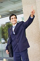Businessman carrying a bag and waving