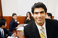 Portrait of a businessman with his colleagues sitting behind him
