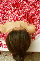 High angle view of a young woman reclining in a bathtub full of rose petals