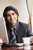 Portrait of a businessman sitting in front of a laptop and smiling