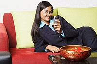 Portrait of a businesswoman lying on a couch with a mobile phone and smiling